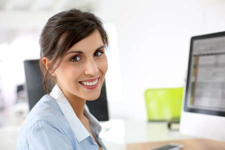 Smiling office worker sitting at desk photo