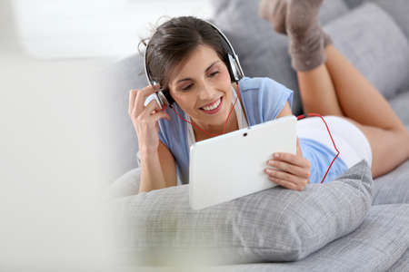 Smiling brunette girl listening to music relaxed on sofa photo
