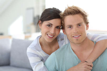 25 years old: Smiling young couple relaxing in sofa at home