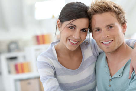 Smiling young couple relaxing in sofa at home photo