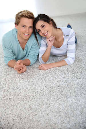 25 years old: Cheerful young couple laying on carpet floor Stock Photo