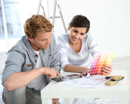 wall paint: Couple in new home choosing wall paint colours