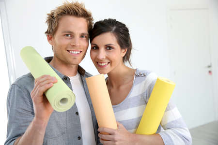 reforming: Portrait of smiling couple holding wallpaper rolls