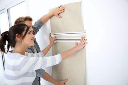 reforming: Young couple choosing wallpaper for new home Stock Photo