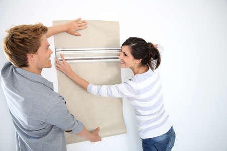 reforming: Joven pareja elegir fondo de pantalla para el nuevo hogar Foto de archivo