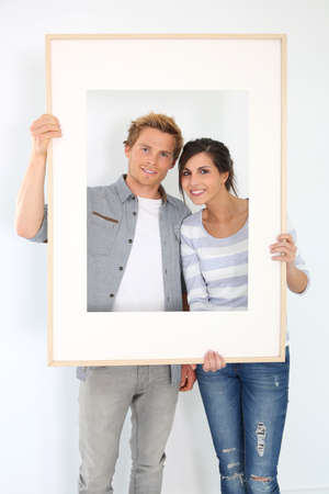 Cheerful young couple holding picture frame to look through Stock Photo