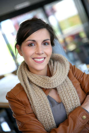 Beautiful brunette girl standing in coffee shop after class photo