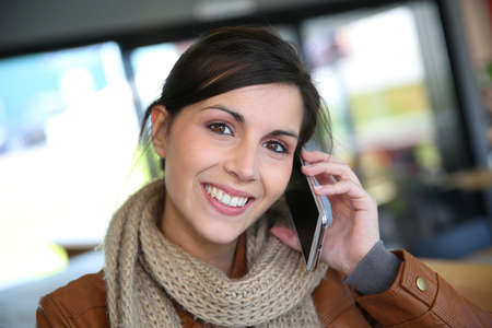 Smiling brunette girl using smartphone in coffee shop photo