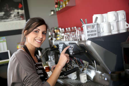 Waitress serving coffee from machine photo