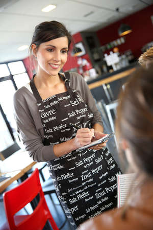Smiling young waitress taking order in restaurant photo