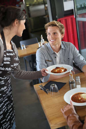 Cheerful young waitress serving dish to customers in restaurant photo