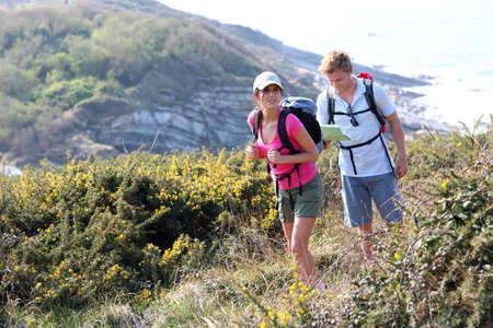 parejas caminando: Pareja de excursionistas en campo del país por el océano Foto de archivo