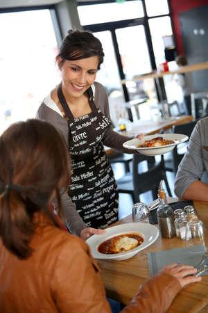 Cheerful young waitress serving lasagna to customers  photo
