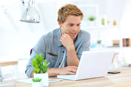 Young man in office working on laptop computer photo