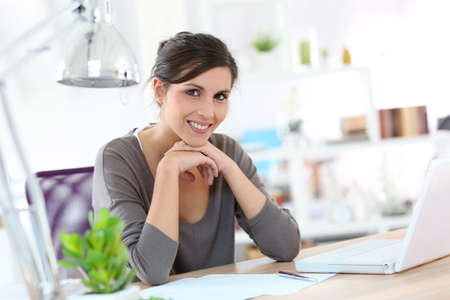 Smiling young woman designer working on laptop