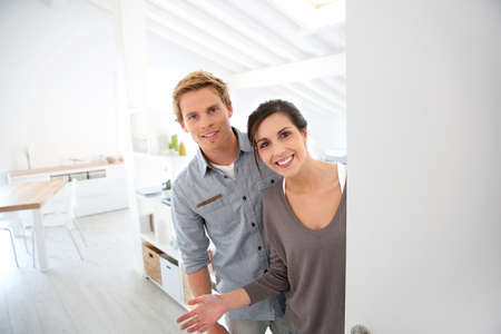 Young couple inviting people to come in new place photo