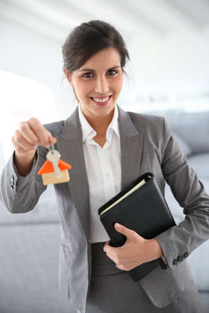 Smiling real-estate agent holding home key t photo