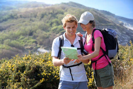 ecotourism: Hikers in country path looking at map Stock Photo