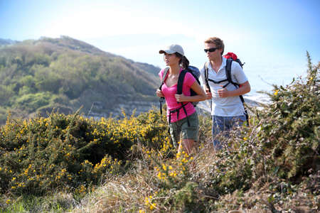 ecotourism: Couple of hikers in country field by the ocean Stock Photo