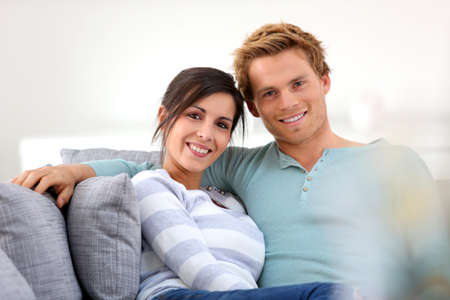 Cheerful young couple relaxing in sofa photo