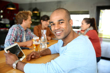 Young man sitting at lounge table with tablet photo