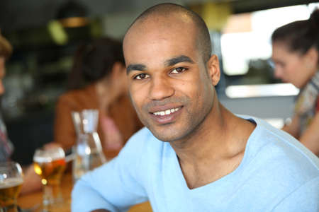 Smiling mixed-raced man sitting in snack bar photo
