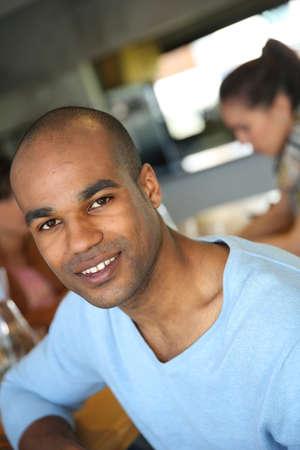 casse-cro�te: Portrait d'un homme souriant assis dans un snack-bar Banque d'images