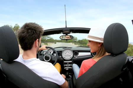 Young couple driving convertible car photo