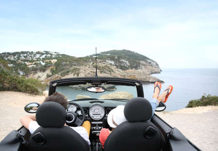 Couple sitting in convertible car and looking at panorama photo