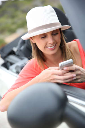 people travelling: Trendy girl in convertible car using smartphone Stock Photo