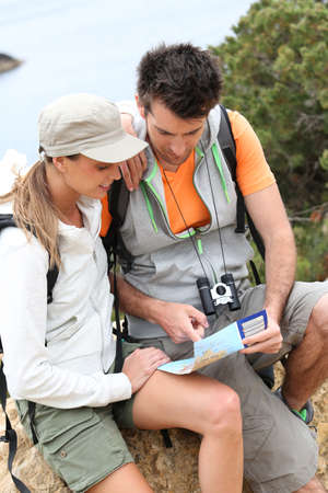 Couple of hikers reading orientation map photo