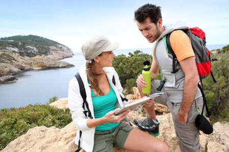 stone tablet: Couple of hikers reading map and using tablet Stock Photo