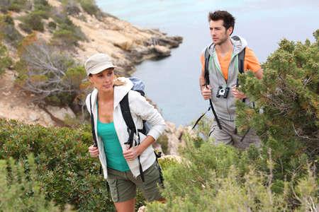 Couple of trekkers climbing island creek photo