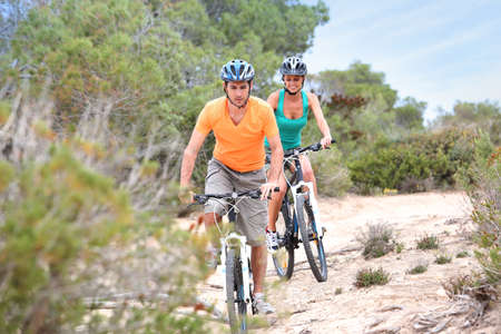 Couple riding bikes on island trail photo