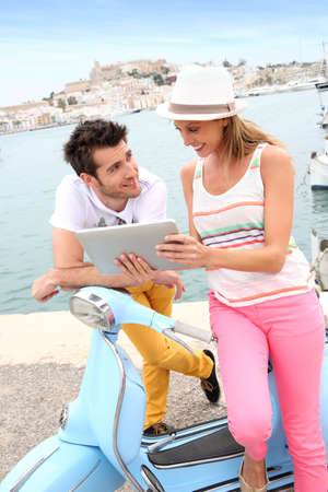Couple of tourists websurfing with tablet, town of Ibiza photo