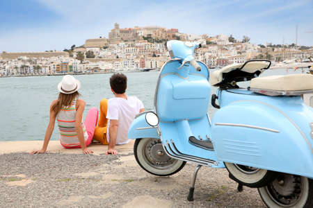 moto: Tourists looking at the town of Ibiza, moto in foreground Stock Photo