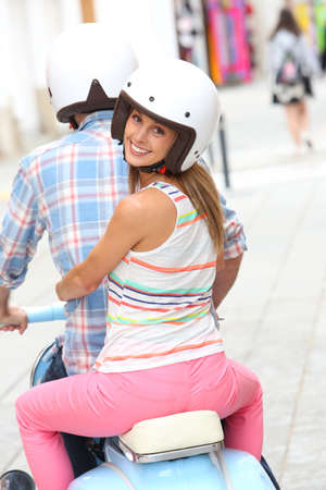 Cheerful couple riding blue moto photo