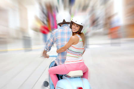 Cheerful couple riding blue moto photo