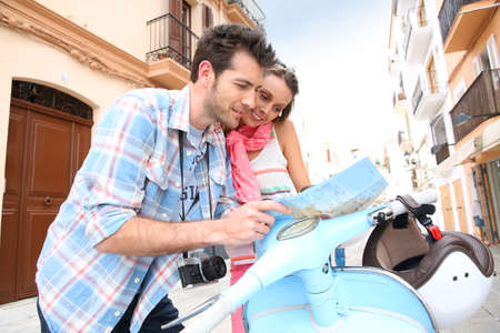 Tourists in Ibiza with scooter looking at city map  photo