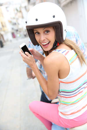 Cheerful girl riding motorcycle and using smartphone photo