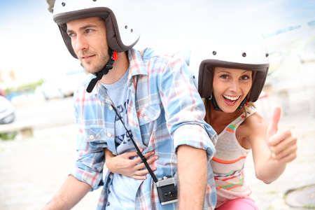 scooter: Girl riding moto with boyfriend and showing thumb up