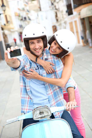 Couple taking picture of themselves on scooter photo