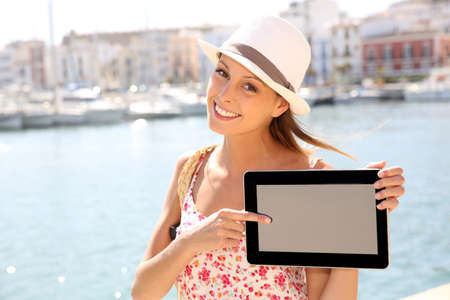 Beautiful tourist girl showing tablet screen photo