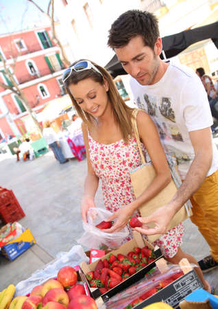Couple of tourists in town buying fruits from local market photo