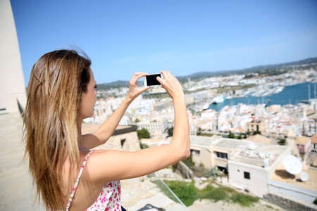 Young woman taking picture of Ibiza town scenery photo