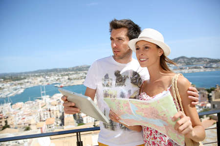 Couple of tourists reading map at the top of Ibiza old town