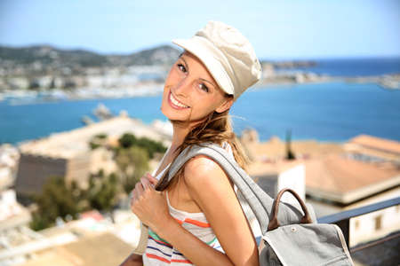 Smiling tourist girl with backpack visiting Balearic Island photo