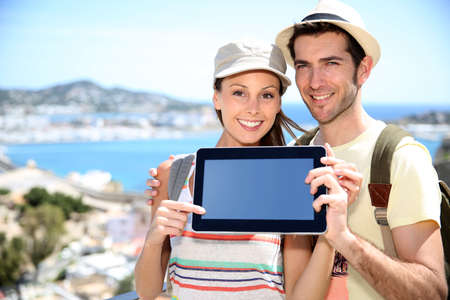 Cheerful couple of travelers showing tablet screen to camera photo