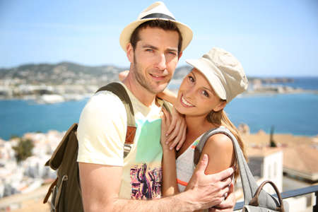 globetrotter: Cheerful couple of tourists with hat and backpack Stock Photo