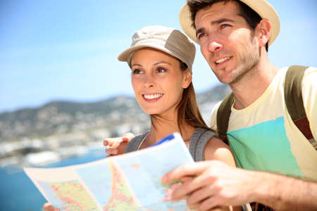 Cheerful young couple of travelers reading city map  photo